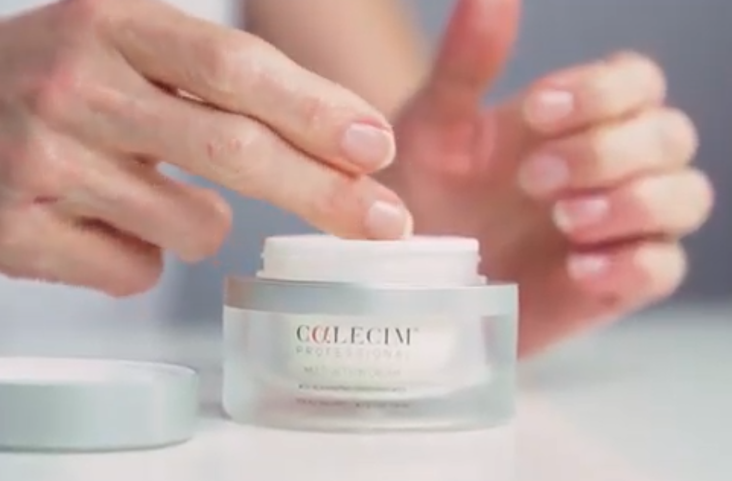 Woman dipping fingers into tub of skin cream enhanced with growth factor ingredients
